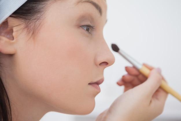 Closeup woman putting on makeup
