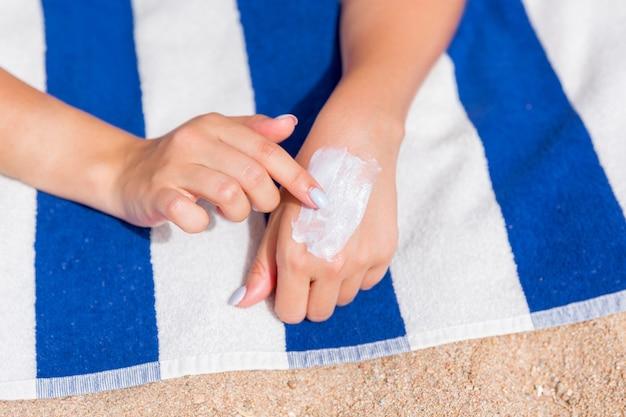 Closeup of woman putting sun cream on hand before sunbathing at the beach.