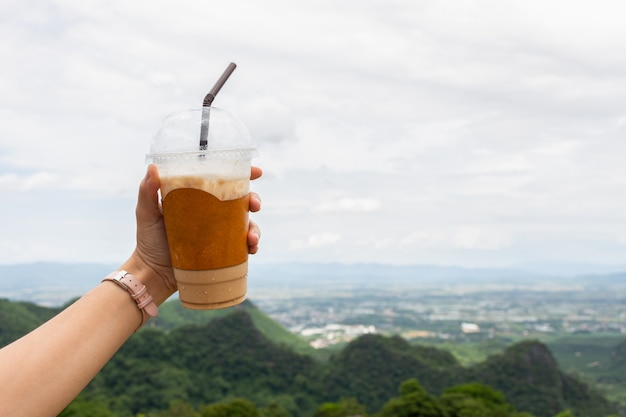 Closeup of woman's hand show cup of espresso iced coffee with mountain view
