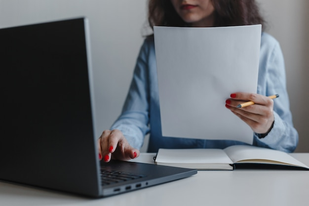 Closeup of woman's hand with red nails holding documents and sitting in front of a laptop wearing blue shirt.
