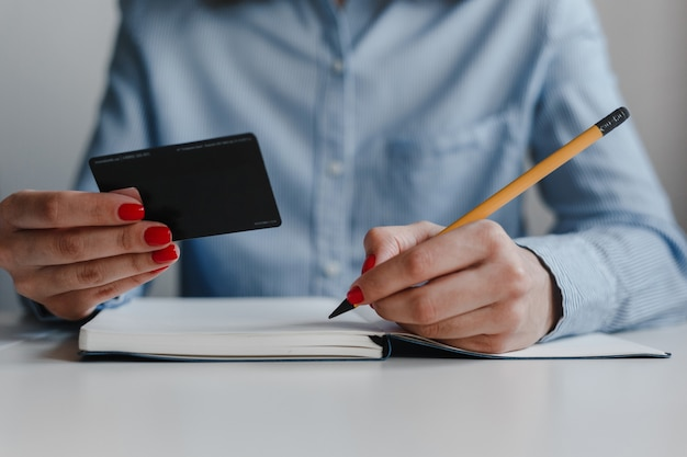Closeup of woman's hand with red nails writing in notebook with a yellow pencil and holding credit card wearing blue shirt.