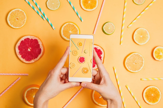 Closeup of woman's hand with a smartphone making picture of various citrus fruits flatlay arrangement. selective focus. food photography or blogging concept.