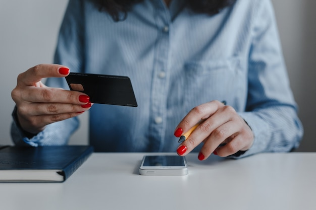 Closeup of woman's hands with red nails holding credit card and clicking mobile phone making payment online