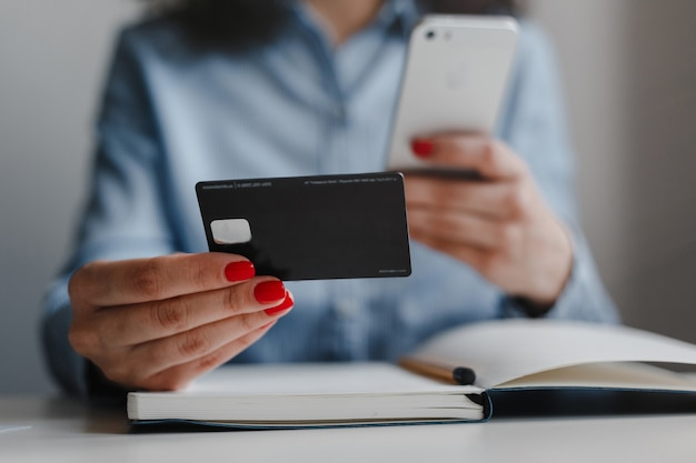 Closeup of woman's hands with red nails holding credit card and mobile cell phone making payment online wearing blue shirt.