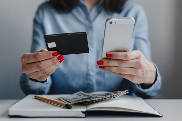 Closeup of woman's hands with red nails holding credit card and phone wearing blue shirt sitting at a desk, making payment online.