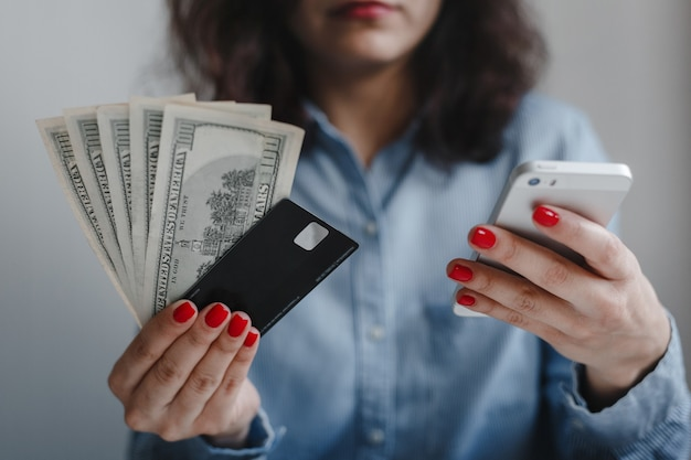 Closeup of woman's hands with red nails holding hundred dollars money banknotes, credit card and phone