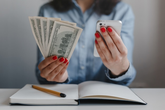 Closeup of woman's hands with red nails holding hundred dollars money banknotes and a mobile