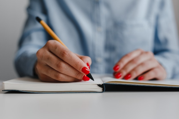 Closeup of woman's hands with red nails making notes in a notebook at the desk.