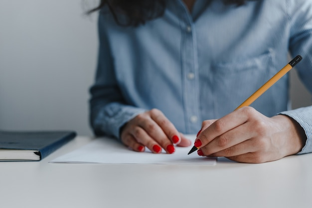 Closeup of woman's hands with red nails signing and correcting documents at the desk.