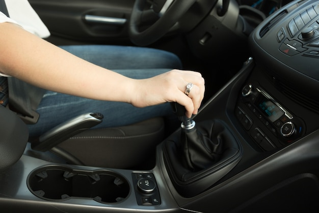 Closeup of woman shifting gear stick and driving a car