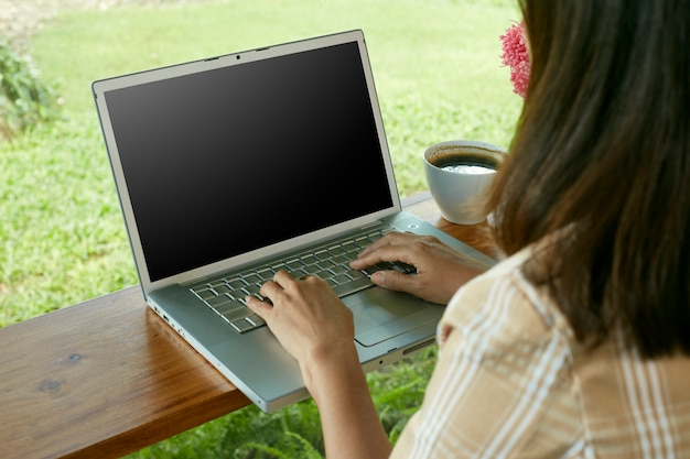 Closeup of woman sitting at home using laptop