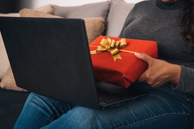 Closeup of a woman talking to her friends on a laptop and showing them a red gift box
