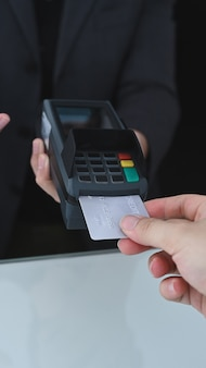 Closeup of woman using credit card swiping machine to payment.
