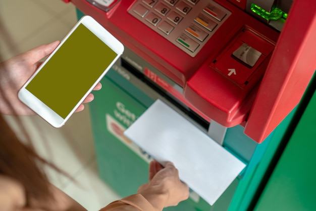 Closeup woman using the smart mobile phone for withdrawing the cash and scanning the barcode