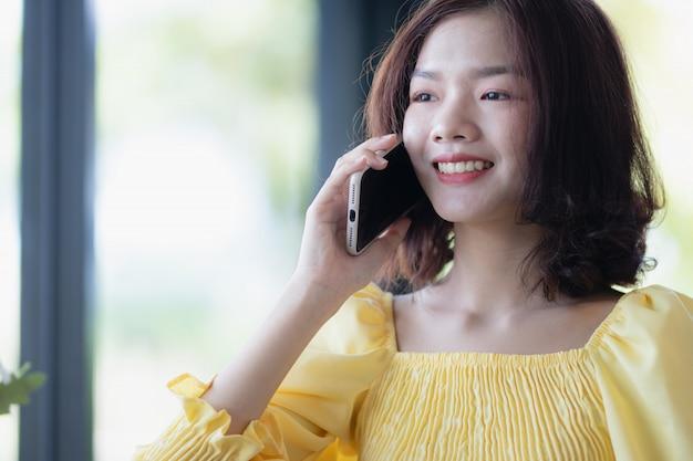 幸せでスマートフォンを使用してクローズアップの女性。