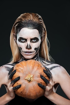 Closeup of woman with gothic skeleton makeup holding pumpkin over black background