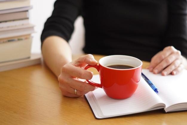 Primo piano di una donna che lavora o studia da casa con un caffè rosso in mano