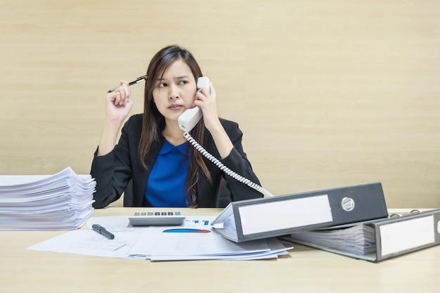 Closeup woman working with document file and hold office phone in her hand