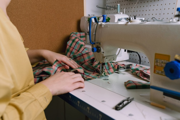 Closeup of a woman working with sewing machine in her workshop