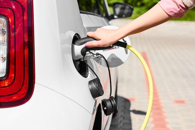 Рука женщины крупного плана держа штепсельную вилку зарядного устройства электрического автомобиля. автомобиль с нулевым уровнем выбросов