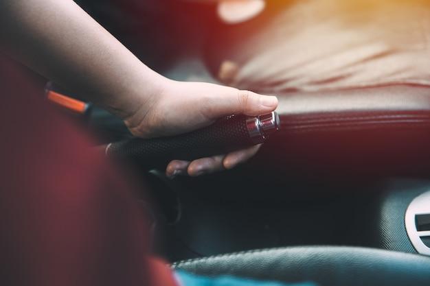 근접 촬영 여성 드라이버 손을 잡고 자동차 핸드 브레이크 빈티지 컬러 톤