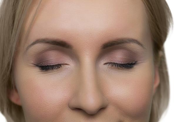 흰 벽에 닫힌 눈과 화장과 근접 촬영 여성 얼굴