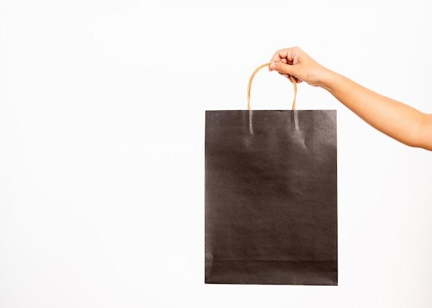 黒い買い物袋を持っているクローズアップの女性の手