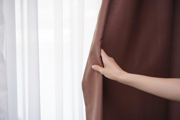 Closeup of women hand opening curtain