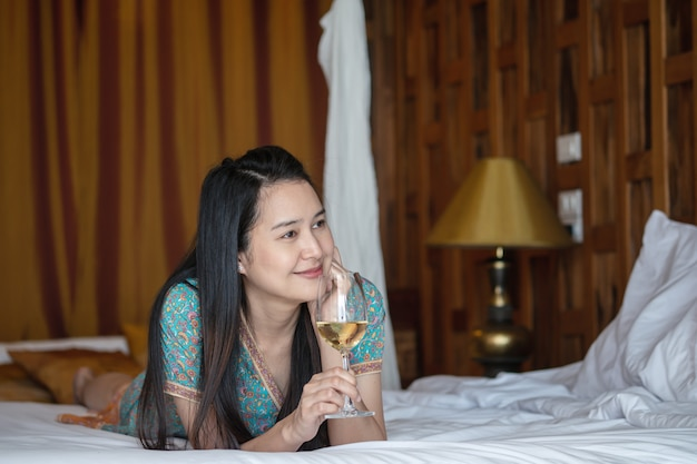 Closeup women lie on bed with white wine glass in bedroom