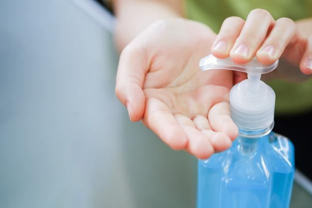 クローズアップ女性は手を洗い、洗浄用の青いアルコールゲルボトルとコロナウイルスの発生を止めるための医療用サージカルマスク。ウーハンコロナウイルスとエピデミックウイルスの症状。