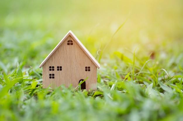 Деревянный модельный дом крупным планом на фоне травы солнечного света