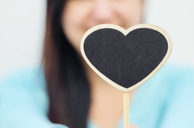 Closeup wooden black board in heart shape with blurred smile face of woman background