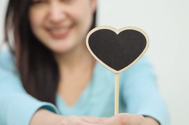 Closeup wooden black board in heart shape with blurred smile face of woman