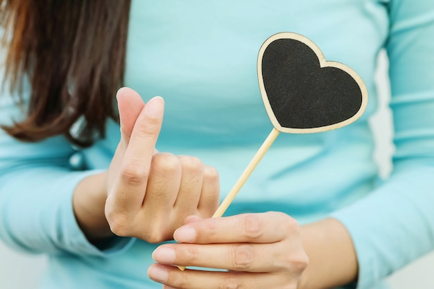 Closeup wooden black board in heart shape with finger of woman in mini heart symbol