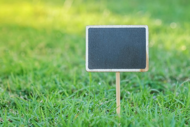Closeup wooden black board in square shape on green grass in the park textured background