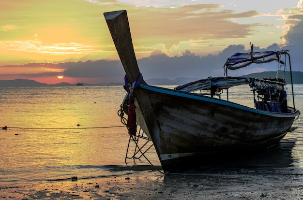 Primo piano di una barca di legno sulla spiaggia circondata dal mare sotto un cielo nuvoloso durante il tramonto