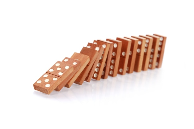 Closeup of the wooden dominoes falling on a white surface