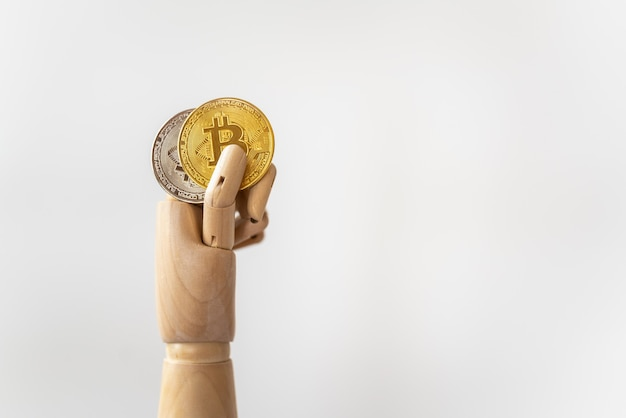 Closeup of wooden hand model holding gold and silver bitcoin coins on white.