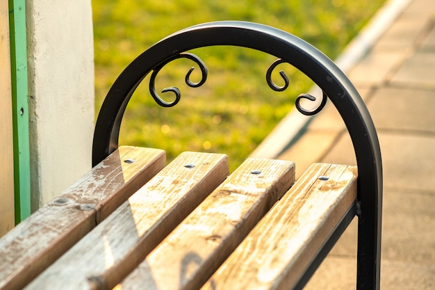 Closeup of wooden park bench with metal handgrip outdoors.