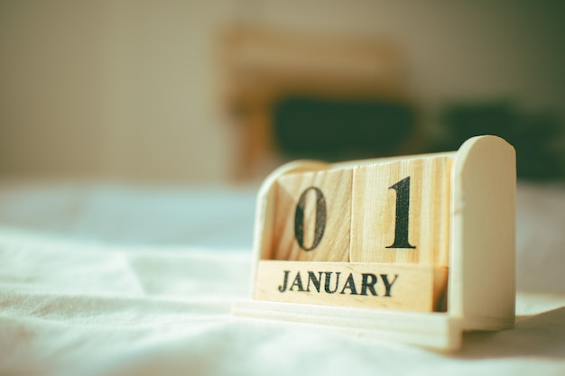 Closeup of wooden pieces with tex 01 january in the concept of new year.