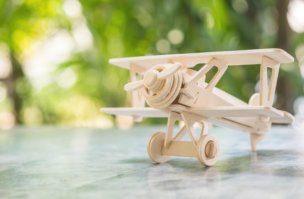 Closeup wooden plane model on blurred marble table in the garden background