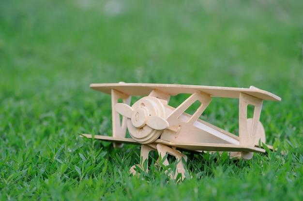 草の床の背景にクローズアップ木製飛行機のおもちゃ