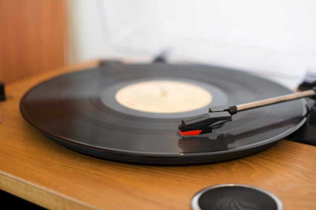 Closeup of a wooden record player with a vinyl playing music