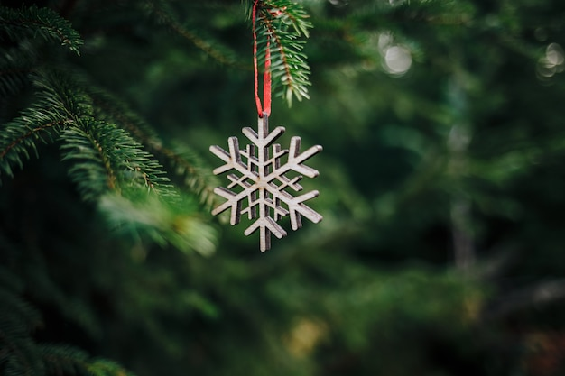 Closeup of a wooden snowflake-shaped christmas ornament on a pine tree