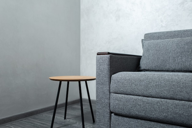 Closeup of wooden table and sofa on background of textured walls of apartment.