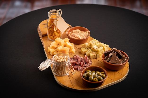 Primo piano di una traccia di legno con assortimento di formaggi, olive verdi, barrette di cioccolato