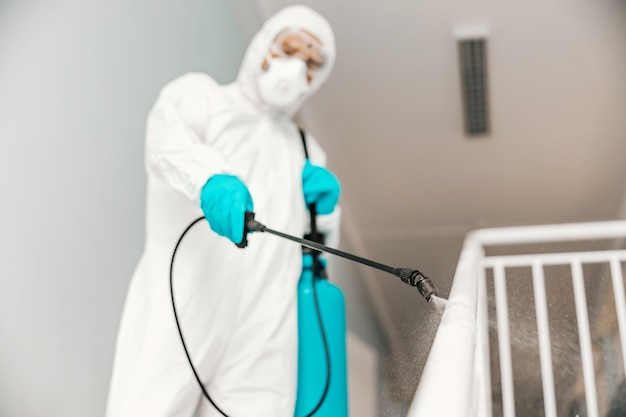 Closeup of worker in sterile uniform, with gloves and facial mask sterilizing railing in school