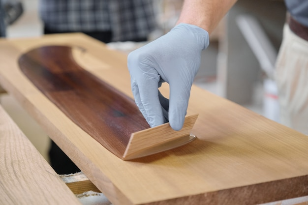 Closeup of workers hand covering wooden plank with finishing protective cover for wood
