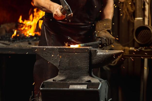 남성 대장장이의 강력한 손으로 작업하는 근접 촬영은 대장장이에서 철 제품을 위조합니다