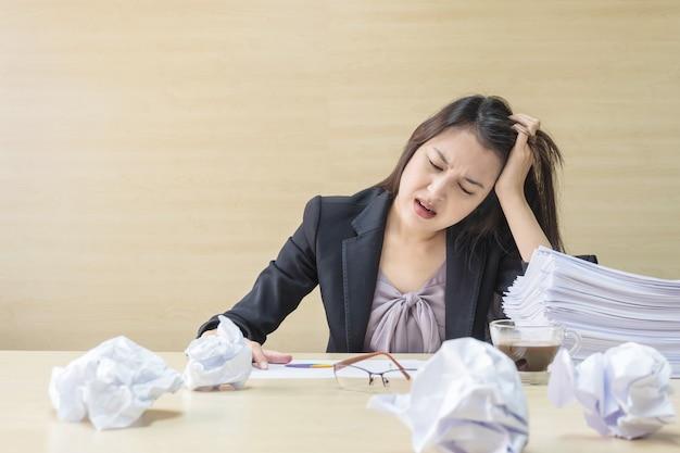 Работающая женщина крупного плана подчеркнута от кучи бумаги работы перед ей в концепции работы на запачканном деревянном столе